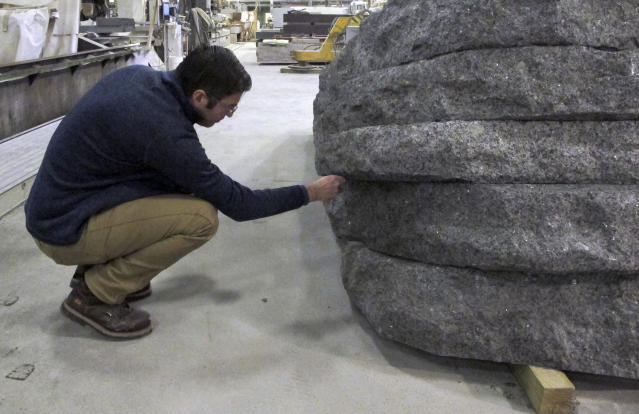 In this Tuesday, Jan. 8, 2019 photo, architect Michael Arad, a designer of the World Trade Center memorial, examines a granite monolith being created at the Rock of Ages in Barre, Vt. The monolith is one of six that will be part of a permanent dedication to ground zero rescue and recovery workers expected to be unveiled in late May at the National September 11 Memorial & Museum in New York. (AP Photo/Lisa Rathke)