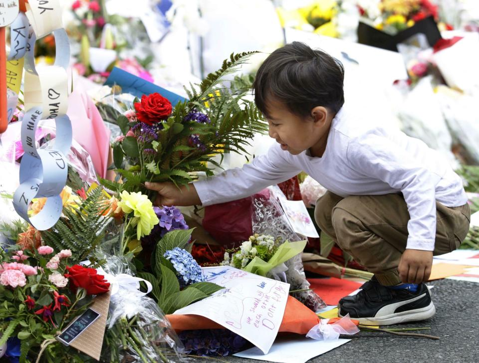 A child offers flowers near the Al Noor mosque in Christchurch on March 19. Source: AAP