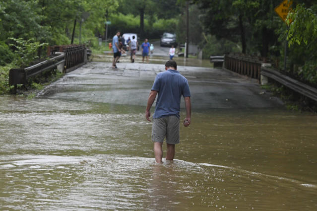 <p>A man checks the depth of the water on Circle Drive Ruxton Road. (Photo: Jerry Jackson, Baltimore Sun via AP) </p>