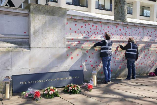 People painting red hearts on the memorial