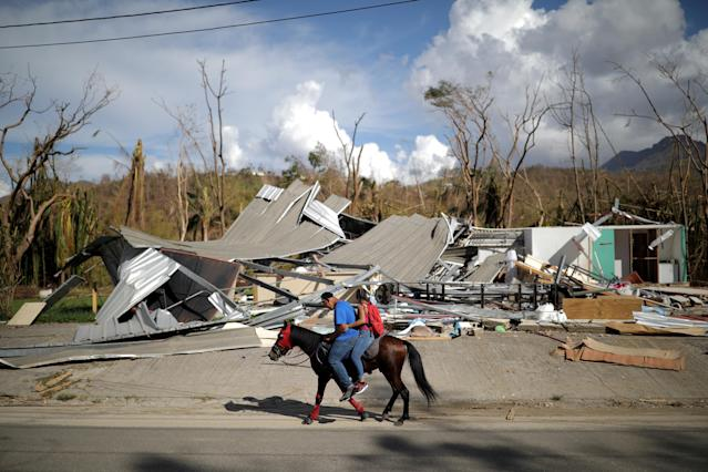 <p>Local residents ride a horse by a destroyed building after Hurricane Maria in Jayuya, Puerto Rico, Oct. 4, 2017. (Photo: Carlos Barria/Reuters) </p>