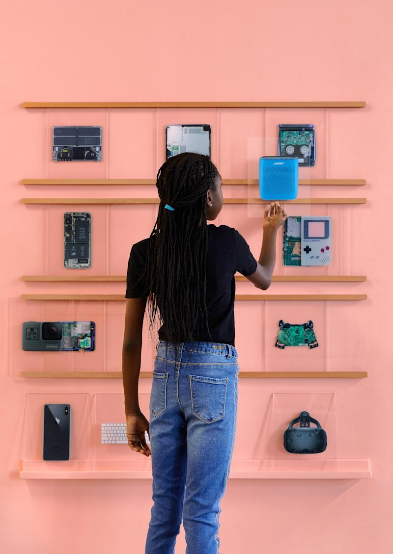 A young girl studies the inner makings of various devices on the wall.