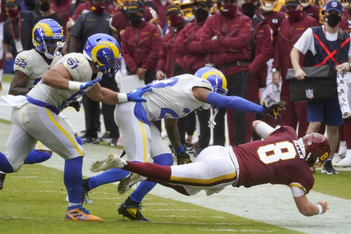 Los Angeles Rams' Jalen Ramsey tacles Washington Football Team's Kyle Allen during the first half of an NFL football game Sunday, Oct. 11, 2020, in Landover, Md. Allen left the game with an injury. Ramsey was penalized for the hit. (AP Photo/Steve Helber)