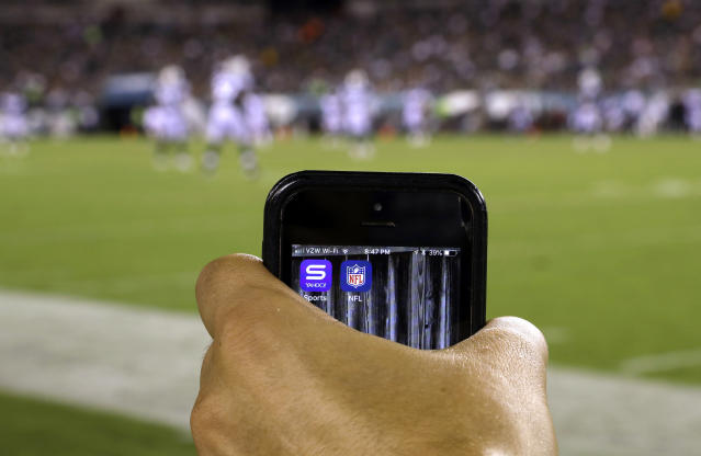 In this Thursday, Aug. 30, 2018, photo a phone screen is displayed during the second half of a preseason NFL football game between the Philadelphia Eagles and the New York Jets in Philadelphia. As the regular season starts Thursday, Sept. 6, the league is finally dropping a requirement that viewers sign in with a cable or satellite subscription, as it seeks to expand its online audience at a time when TV ratings are declining. The subscription-free games will be available on the NFL app and the Verizon-owned Yahoo Sports, Tumblr and AOL apps. (AP Photo/Matt Rourke)