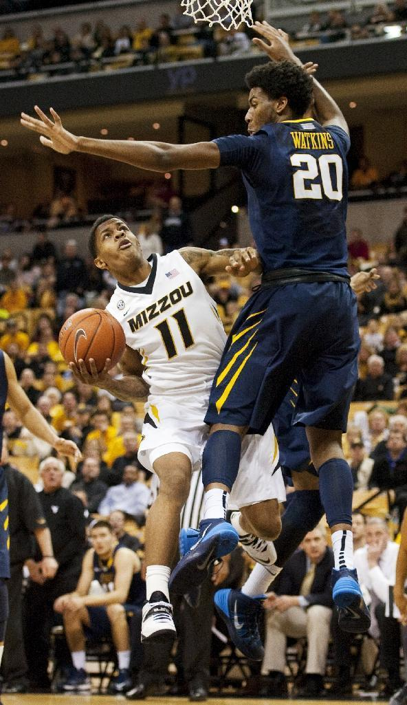 Missouri's Shane Rector, left, tries to shoot past West Virginia's Brandon Watkins, right, during the first half of an NCAA college basketball game Thursday, Dec. 5, 2013, in Columbia, Mo. (AP Photo/L.G. Patterson)