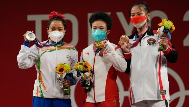 Weightlifter Mirabai Chanu poses with a silver medal around her neck on the women's 49kg podium. AP