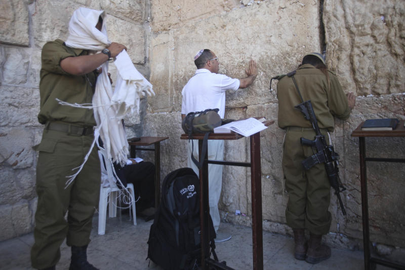 In this Monday, July 2, 2012 Israeli soldiers pray next to the Western Wall, the holiest site where Jews can pray, in Jerusalem's Old City. Deep in the heart of Mea Shearim, a Jerusalem bastion of hardline ultra-Orthodox Jews, hundreds of bearded young men in black suits have their noses burrowed into books, immersed in biblical study and oblivious to their surroundings. These young men, and their sheltered lifestyle, are at the heart of a battle that is tearing Israel apart in a clash between tradition and modernity, religion and democracy. The fight centers on whether ultra-Orthodox males should be drafted into the military along with other Jews, but it really is about a much deeper issue: the place of Judaism in the Jewish state. (AP Photo/Dan Balilty)