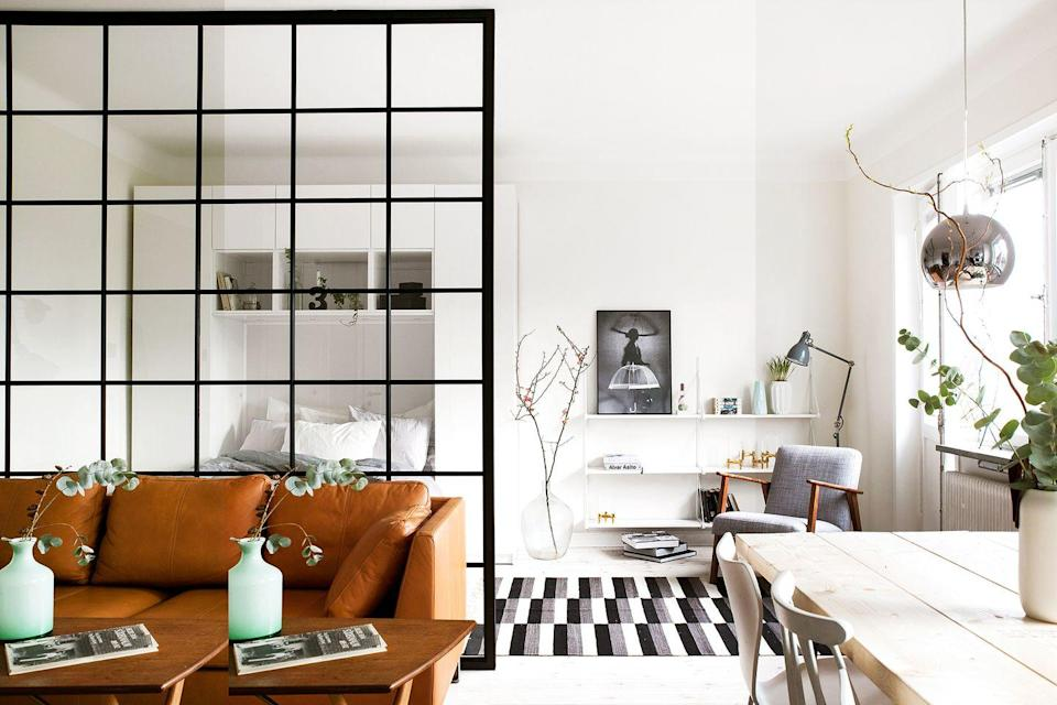 <p>The floating shelves in this neutral-toned Scandinavian studio apartment blend in seamlessly with the white walls. Take inspiration from this space if you're working within a smaller scale space and want your floating shelves to disappear instead of distract. </p>