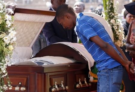 A mourner pays his last respects to Robert Mugabe's body as it lies in state at the at Rufaro stadium