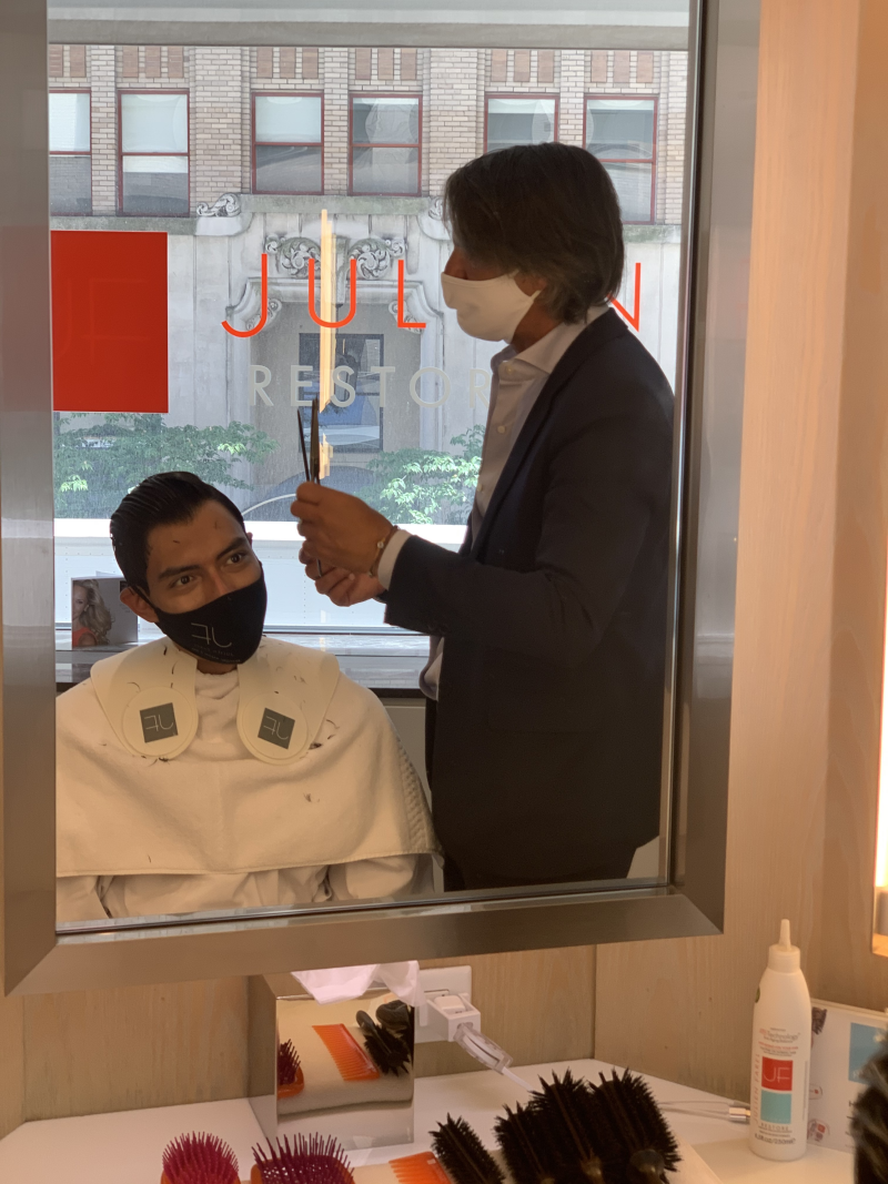 Julien Farel cutting client's hair in newly reopened salon.