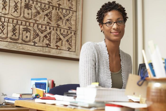 A smiling woman sitting at her desk