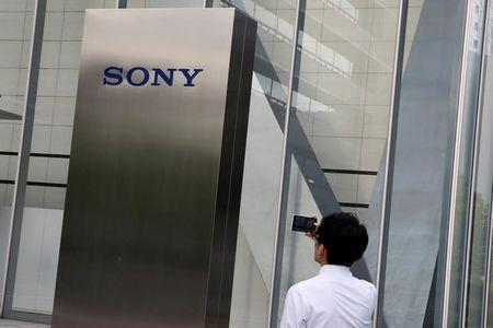 A man takes a picture of the Sony brand logo outside the headquarters of Sony Corp in Tokyo