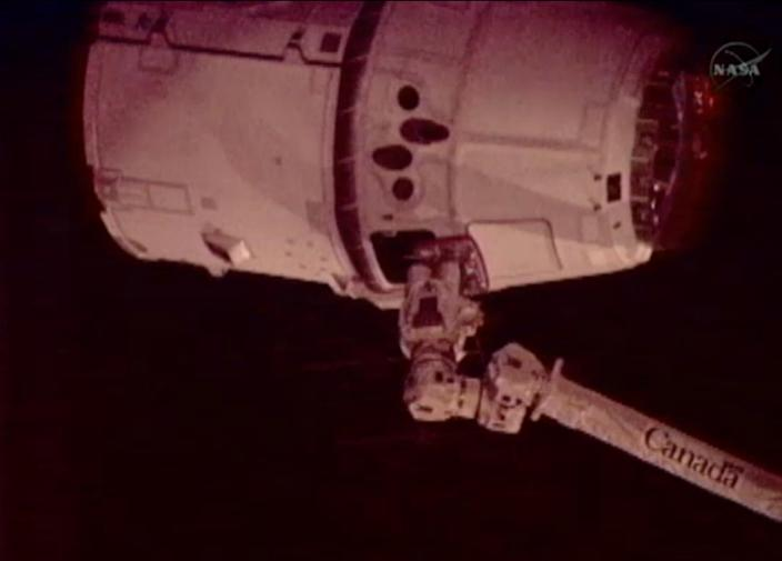 This image provided by NASA-TV shows the SpaceX Dragon commercial cargo craft, top, just after Dragon was grappled by the Canadarm2 robotic arm and connected to the International Space Station, Friday, May 25, 2012. Dragon is scheduled to spend about a week docked with the station before returning to Earth on May 31 for retrieval. (AP Photo/NASA)
