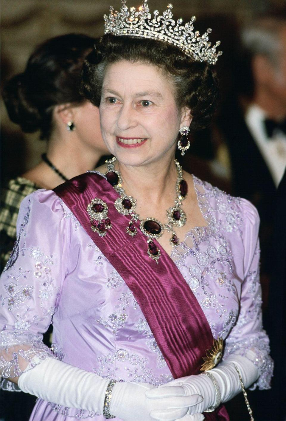 <p>The Queen's striking amethyst set, which includes a diamond brooch, necklace and earrings, is known as the Crown Amethyst Suite of Jewels and it originally belonged to Queen Victoria's mother. Elizabeth is seen wearing it here on March 26, 1985.</p>