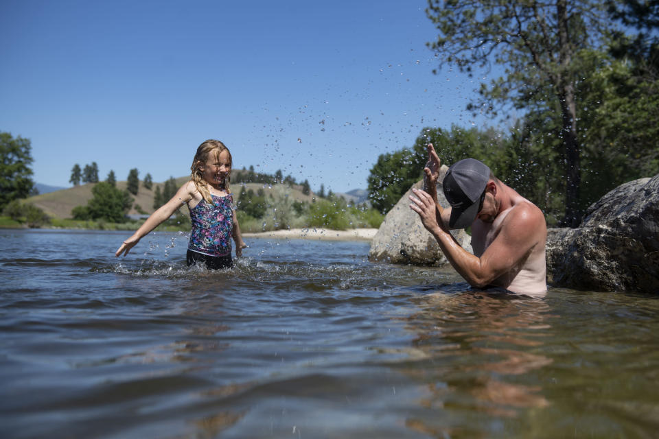 Leighanna Bardgett, 7, splashes her father Jessuah, right, as they cool off in the Bitterroot River as temperatures reached over 100 degrees in Missoula, Montana, on Wednesday, June 30, 2021. (AP Photo/Tommy Martino)