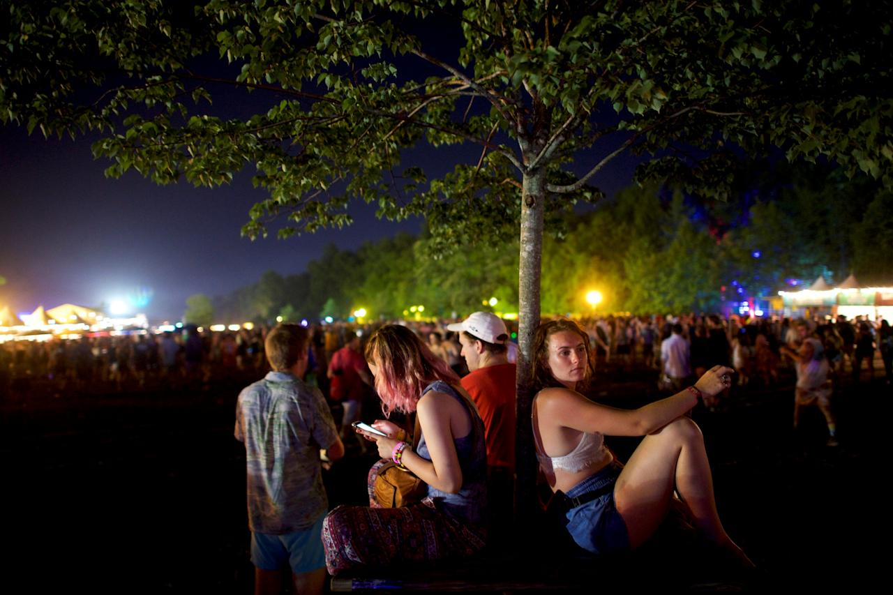Grace Kennedy, 19, rests against a tree while others use their smartphones on the third day of the Firefly Music Festival in Dover, Delaware U.S., June 16, 2018.  REUTERS/Mark Makela