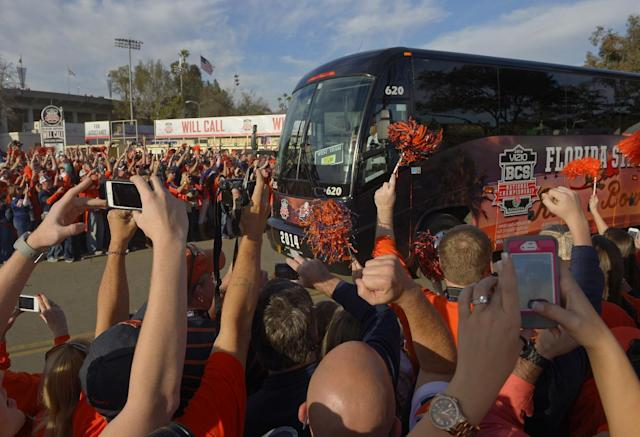 Fans cheer as the Florida State bus arrives to the Rose Bowl before the NCAA BCS National Championship college football game against Auburn Monday, Jan. 6, 2014, in Pasadena, Calif. (AP Photo/Mark J. Terrill)