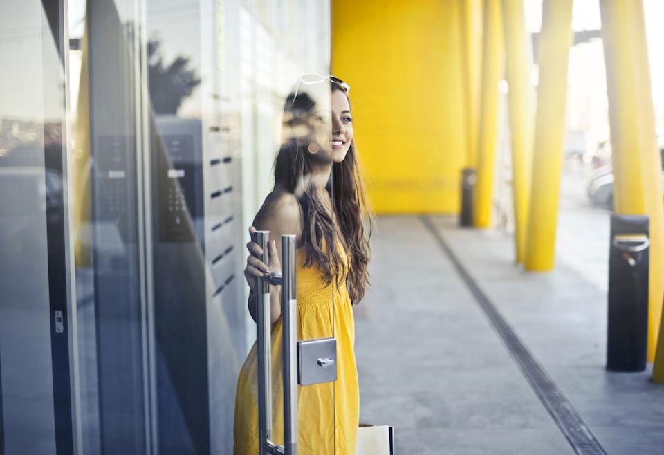 Beautiful girl opening a glass door to exit a building