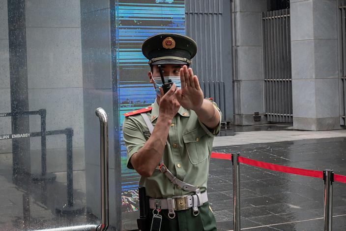 """<p>FILE. A Chinese paramilitary police officer gestures and speaks over his two-way radio while standing at the entrance gate of the Australian embassy in Beijing on July 9, 2020. - China has suspended """"indefinitely"""" its key economic dialogue with Australia.</p> (Photo by NICOLAS ASFOURI/AFP via Getty Images)"""