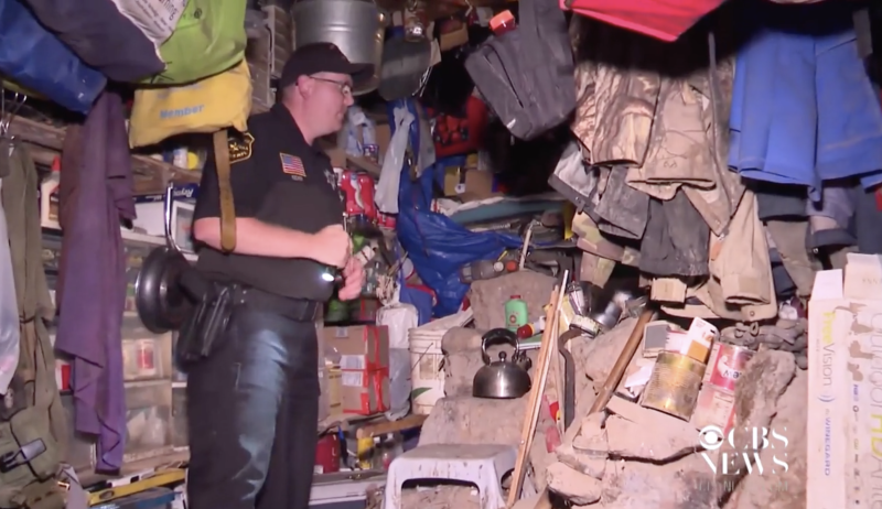 A police officer inspects the inside of the hideout of Jeremiah Button in Wisconsin.