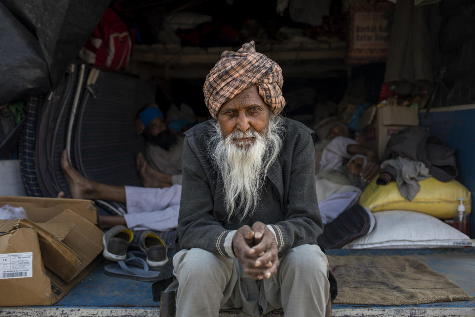 Amrik Singh Mikka, 78, sits for a photograph on the back of his tractor trailer parked on a highway during a protest against new farm bills at the Delhi-Haryana state border, India, Tuesday, Dec. 1, 2020. At night, the farmers sleep inside the trailers or under the trucks. During the day, they sit huddled in groups at the backs of the vehicles, surrounded by mounds of rice, lentils and vegetables. Every day, thousands more join the protesters. (AP Photo/Altaf Qadri)