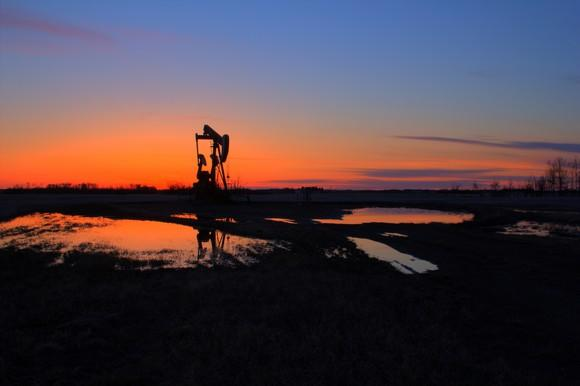 An oil pump with the sun setting behind it.