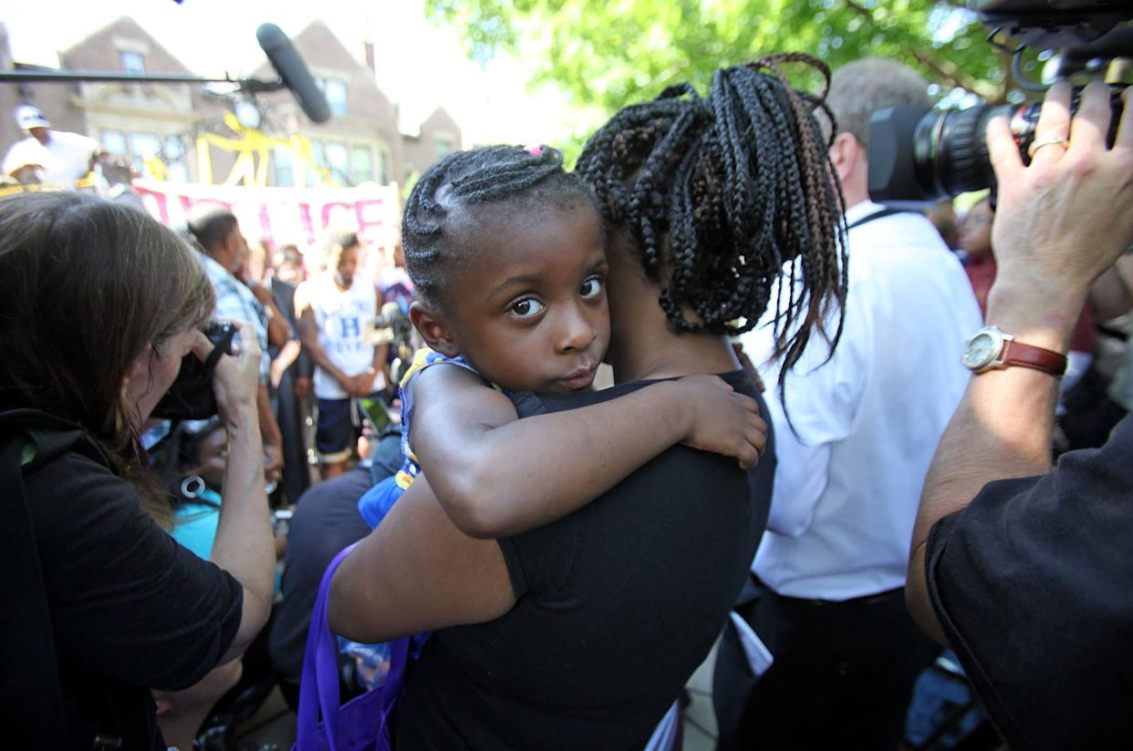 "The four-year-old daughter of Diamond Reynolds, who was in the car when Philando Castile was fatally shot during a traffic stop by police, is held by a friend during a ""Black Lives Matter"" protest in front of the Governor's Mansion in St. Paul, Minnesota, U.S., July 7, 2016."