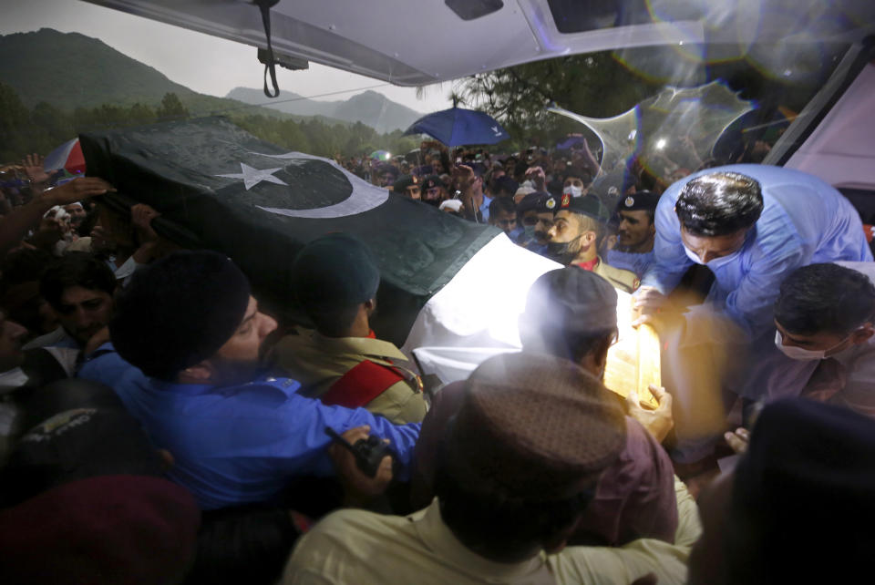 Soldiers and volunteers load the national flag-wrapped casket of Pakistan's nuclear scientist Abdul Qadeer Khan into a vehicle, following a funeral prayer, in Islamabad, Pakistan on Sunday, Oct. 10, 2021. Khan, a controversial figure known as the father of Pakistan's nuclear bomb, died Sunday of COVID-19 following a lengthy illness, his family said. He was 85. (AP Photo/Anjum Naveed)