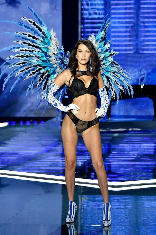 <p>Bella Hadid stepped out at the Shanghai show in a black lingerie set complete with blue feathers and co-ordinating earrings. <em>[Photo: Getty]</em> </p>