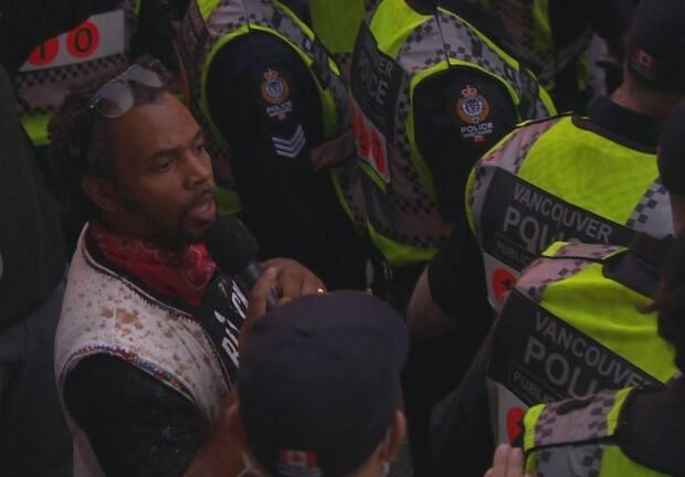 Street preacher David Lynn, founder of Christ's Forgiveness Ministries, delivered a speech in Vancouver's downtown West End surrounded by Vancouver police officers as a crowd of pro-LGBTQ demonstrators surrounded him on August 31, 2020. (Enzo Zanatta/CBC news - image credit)