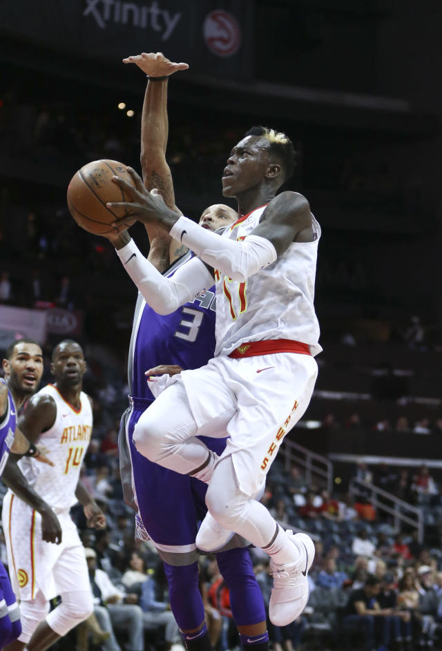 Atlanta Hawks guard Dennis Schroder, right, drives to the basket against Sacramento Kings guard George Hill, left, during the first half of an NBA basketball game Wednesday, Nov. 15, 2017, in Atlanta. (AP Photo/John Bazemore)