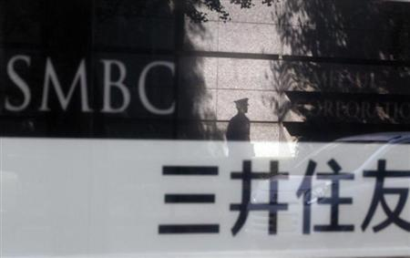 File photo of a security guard reflected on a sign outside a branch of Sumitomo Mitsui Banking Corporation in Tokyo