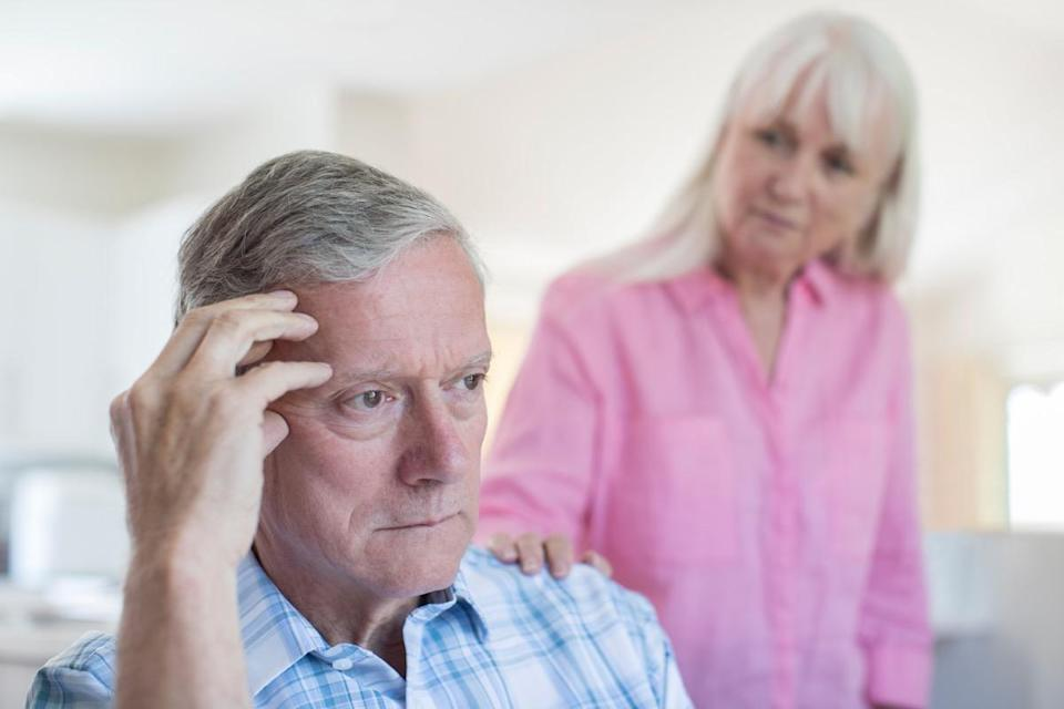 Mature Woman Comforting Man With Depression At Home