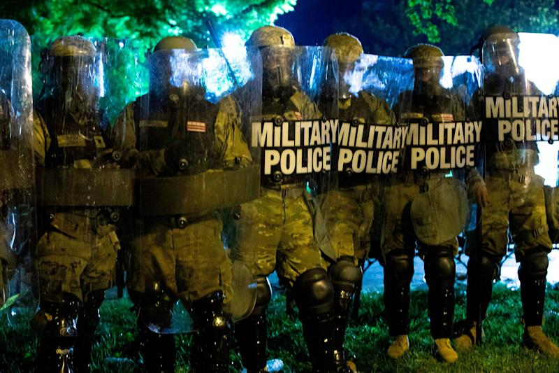 Military police officers watch demonstrators as they chant outside of the White House on May 30 in Washington, D.C., during a protest over Floyd's death. (Photo: JOSE LUIS MAGANA via Getty Images)