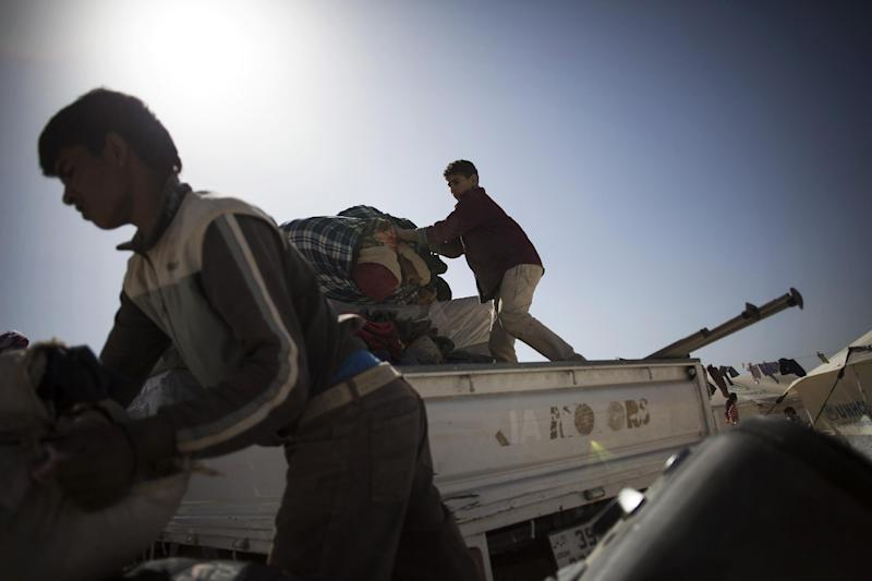 In this Tuesday, Oct. 22, 2013 photo, Syrian refugees unload their belongings after their arrival at the Zaatari refugee camp near the Syrian border in Jordan. With Syria's civil war in its third year, more than 2 million Syrians have fled their country. About 100,000 live in this camp. (AP Photo/Manu Brabo)