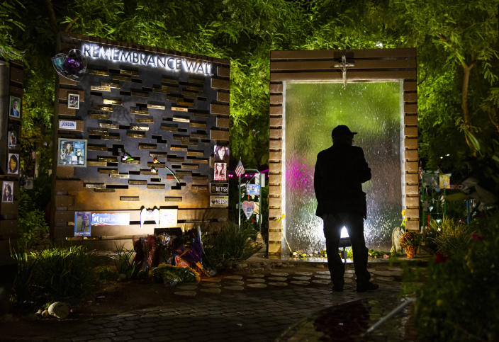 """FILE - In this Oct. 1, 2020, file photo, the Rev. Bill Minson, chaplain for the Las Vegas field office of the United States Secret Service, walks through the Las Vegas Community Healing Garden after candles were lit and names were read in memory of the victims of the shooting at a remembrance ceremony in Las Vegas. A public panel planning a permanent Las Vegas memorial honoring victims of the deadliest mass shooting in modern U.S. history heard that there's no perfect answer to how a tribute should look and feel. """"The goal is to provide comfort and hope and facilitate healing,"""" Anita Ahuja, manager of mass violence response for the California Victim Compensation Board, advised the 1 October Memorial Committee during its initial meeting Nov. 25, 2020. (Chase Stevens/Las Vegas Review-Journal via AP, Pool, File)"""