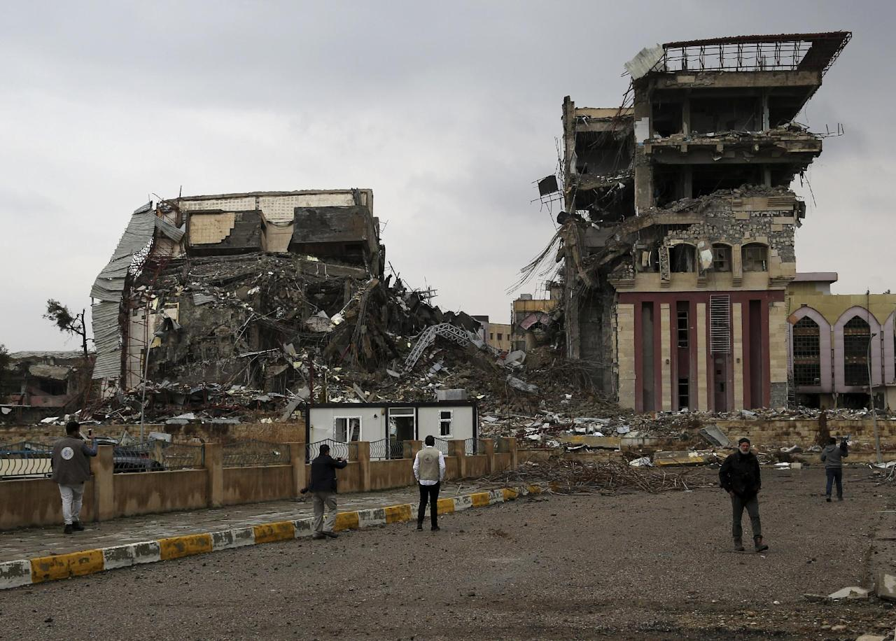 Students inspect their badly damaged university, recently liberated from Islamic State militants on the eastern side of Mosul, Iraq, Sunday, Jan. 22, 2017. (AP Photo/ Khalid Mohammed)