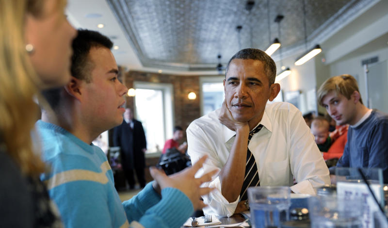 President Barack Obama listens to Andres Cruz, second from left, as he has lunch with five young people at The Coupe restaurant in the Columbia Heights section of Washington, Friday, Jan. 10, 2014. The five are spearheading creative outreach efforts to connect with and help enroll young consumers through the Marketplaces or are interested in getting more involved with these efforts. Seated at the table with Obama at left is Anne Johnson. (AP Photo/Susan Walsh)