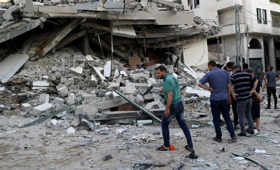 People inspect the rubble of destroyed residential building that was hit by an Israeli airstrike, in Gaza City, Monday, May 17, 2021. (AP Photo/Adel Hana)