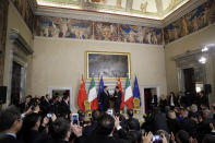"""Chinese President Xi Jinping, background left, meet with Italian Premier Giuseppe Conte during the signing ceremony of a memorandum of understanding at Rome's Villa Madama, Saturday, March 23, 2019. Italy signed a memorandum of understanding with China on Saturday in support of Beijing's """"Belt and Road"""" initiative, which aims to weave a network of ports, bridges and power plants linking China with Africa, Europe and beyond. (AP Photo/Andrew Medichini)"""