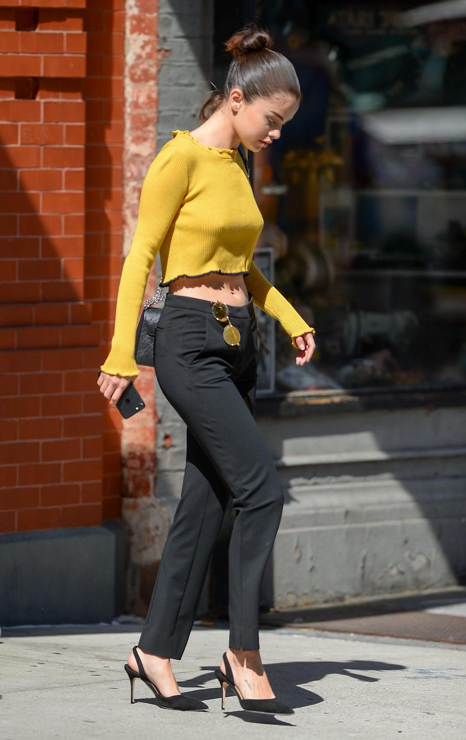 """<p>Selena reminded us all that a <a href=""""https://www.popsugar.com/fashion/Selena-Gomez-Wearing-Yellow-Crop-Top-44081586"""" class=""""link rapid-noclick-resp"""" rel=""""nofollow noopener"""" target=""""_blank"""" data-ylk=""""slk:flirty crop top"""">flirty crop top</a> can go a long way on the streets of Soho in September 2017. You'll notice her marigold For Love &amp; Lemons shirt first, but trousers never looked so sexy and '90s inspired! Clip your shades on the waistband and wear sharp slingbacks like Selena, and you'll be turning up the heat.</p>"""