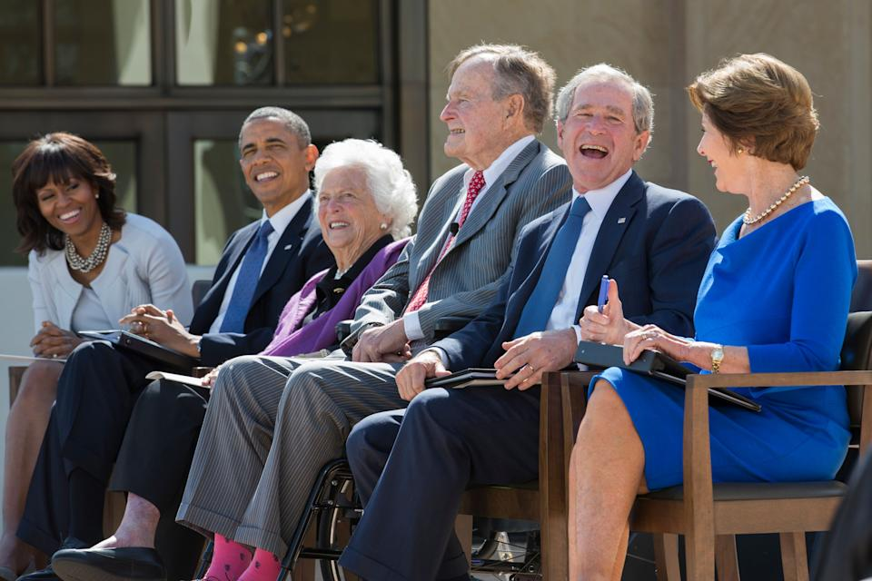 Former President George W. Bush laughs with his father, George H.W. Bush, at the dedication of the George W. Bush presidential library on the campus of Southern Methodist University on April 25, 2013, in Dallas. On the left are first lady Michelle Obama, President Barack Obama and former first lady Barbara Bush. On the right is former first lady Laura Bush.