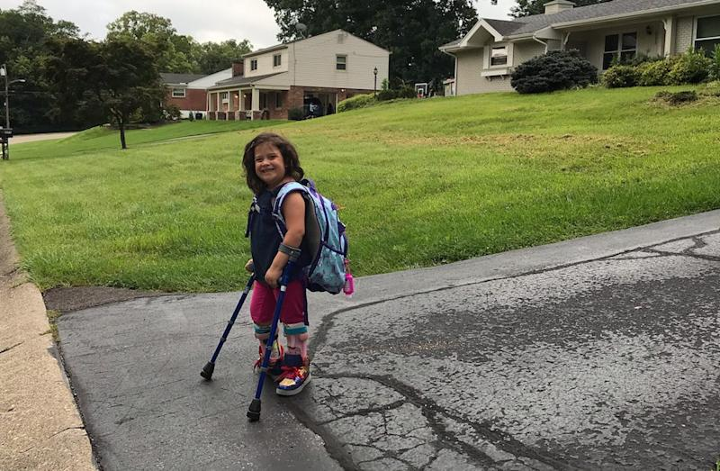 Waiting at the end of the driveway for the bus; girl who uses lofstrand crutches