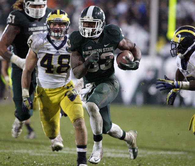 Michigan State's Jeremy Langford (33) runs between Michigan's Desmond Morgan (48) and Raymon Taylor, right, for a 40-yard fourth-quarter rushing touchdown during an NCAA college football game, Saturday, Nov. 2, 2013, in East Lansing, Mich. Langford had 120 yards rushing in Michigan State's 29-6 win. (AP Photo/Al Goldis)