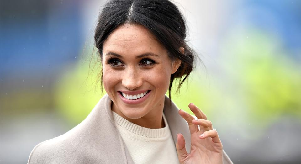 Meghan Markle waves to the crowd at a public event