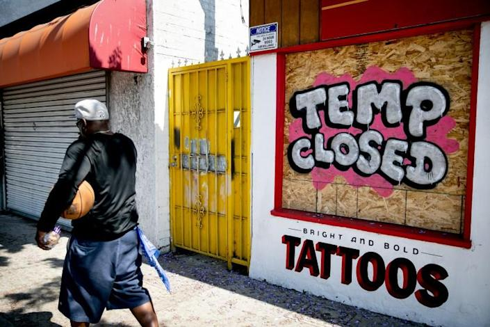 A tattoo parlor on El Cajon Boulevard has its windows boarded up on May 28, 2020 in San Diego, California.