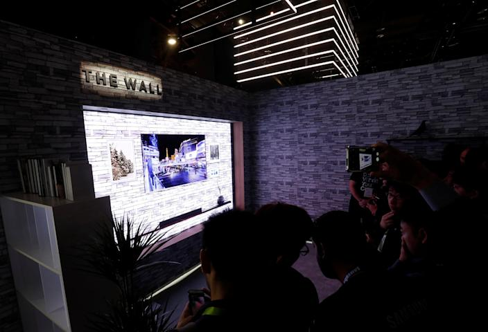 People take photos of The Wall, the world's first consumer modular MicroLED 146-inch TV, in the Samsung Electronics booth at the Las Vegas Convention Center during the 2018 CES in Las Vegas, Nevada, U.S. January 9, 2018. REUTERS/Steve Marcus