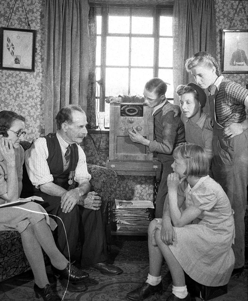 <p>A family gathers around the wireless to listen to the celebration from afar.</p>