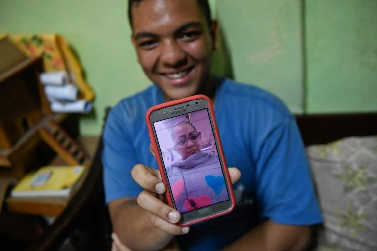 Venezuelan Frankeiber Hernandez, 18, whose parents emigrated to Peru, shows a picture of his mother on his mobile phone at home in the Catia neighborhood in Caracas
