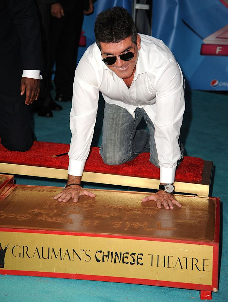 Simon Cowell makes hand prints at the 'The X Factor' Season 2 Premiere Party at Grauman's Chinese Theatre on September 11, 2012 in Hollywood, California.